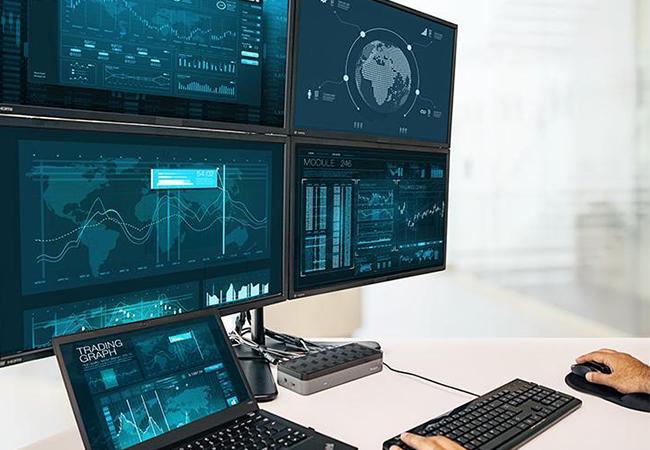 Zu sehen ist ein Arbeitsplatz mit Laptop, vier Monitoren und einer Dockingstation für Laptops, Hände bedienen Maus und Tastatur. Bild: Targus
