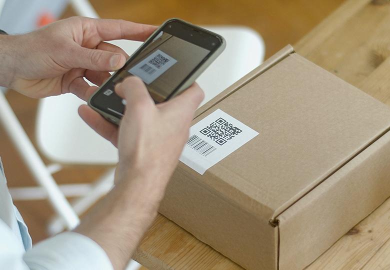 Zwei Hände halten ein Handy und scannen damit den QR-Code auf einem Paket. Es geht um das IT-Sicherheitskennzeichen des BSI. Bild: Pexels/Kampus Production