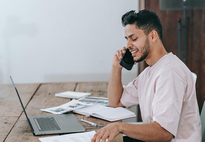 Ein Mann arbeitet im Home Office am Laptop und telefoniert mit dem Smartphone. Die Digitalisierung schreitet voran und verlangt nach einer neuen Cybersicherheitsstrategie 2021. Bild: Pexels/Michael Burrows