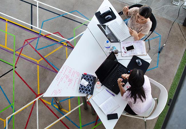 Aus der Vogelperspektive sind zwei Frauen mit Laptops zu sehen, die an einem Schreibtisch gemeinsam arbeiten. Dank Netzwerksicherheit sind die Laptops geschützt. Bild: Pexels/Visual Tag
