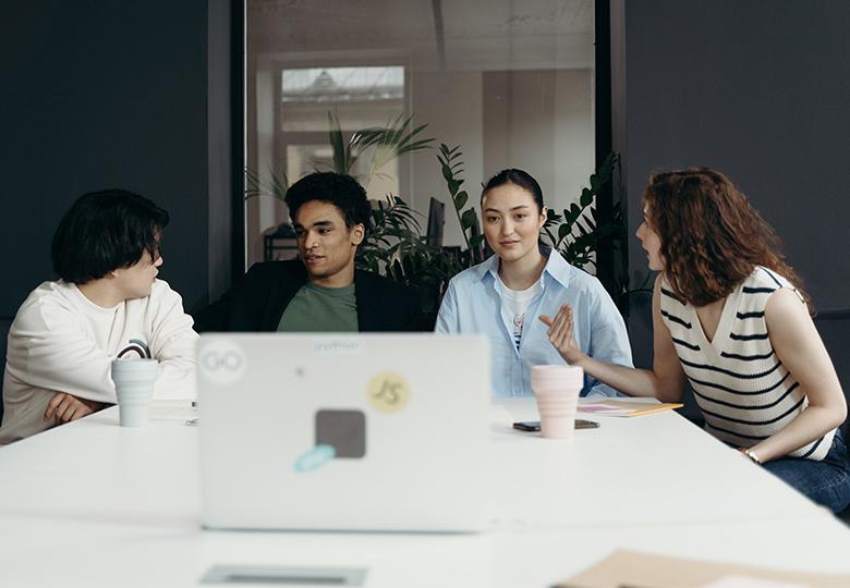 Vier Kollegen sitzen vor einem Laptop, es laufen hybride Meetings. Bild: Pexels/cottonbro