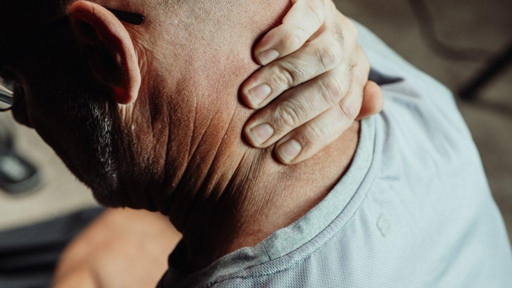 Ein Mann im Home Office fasst sich in den schmerzenden Nacken. Körperliche Beschwerden gehören zu den Home-Office-Nachteilen. Bild: Pexels/Kindel Media