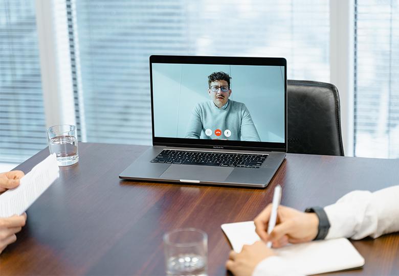 Zu sehen sind die Hände zweier Personen, in der Mitte steht ein Laptop mit einer Videokonferenz auf dem Tisch. Bild: Pexels/MART PRODUCTION